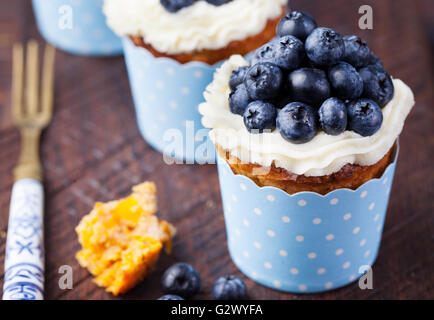 Pumpkin cupcakes with cream cheese, blueberries - Stock Photo