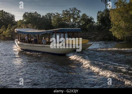 Tourists enjoying a sundowner cruise on the River Zambezi - Stock Photo
