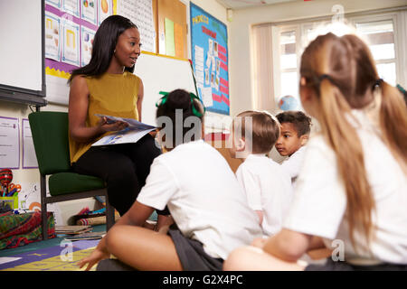 Teacher Reading To Elementary School Pupils In Classroom - Stock Photo