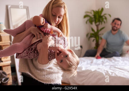 Mother Playing Game With Daughter In Bedroom - Stock Photo