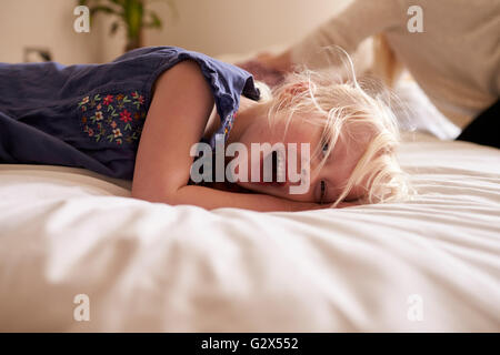 Portrait Of Young Girl Lying On Parent's Bed - Stock Photo