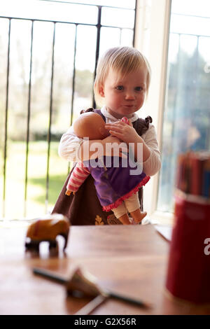 Young Girl Playing With Doll At Home - Stock Photo