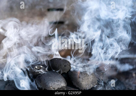To light  coals in a barbecue grill with a lot of smoke - selected focus, narrow depth of field - Stock Photo