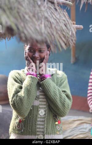 tribal beauty at raiganj village of west bengal,posing near her mud hut - Stock Photo