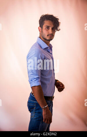 Portrait of brunette young man in light blue shirt and jeans, standing in studio shot against light background - Stock Photo
