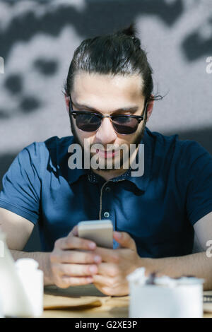 Photo bearded businessman relaxing modern loft office. Banker sitting in vintage chair, looking mobile phone. Using - Stock Photo
