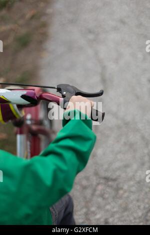 Child hand on the handlebar close up image - Stock Photo
