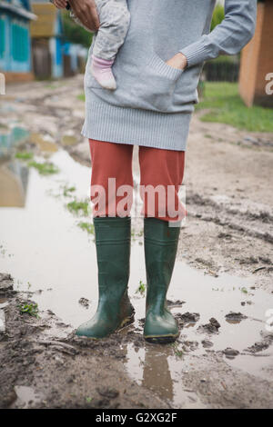woman in rubber boots standing in a puddle - Stock Photo