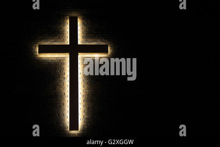 Illuminated Cross. Illuminated cross in horizontal orientation set against a brick wall with copy space. - Stock Photo