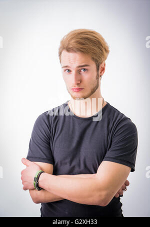 Sad or worried handsome young man looking down, on light background - Stock Photo