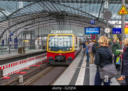Passengers wait for an approaching S Bahn Train at Berlin's Hauptbanhof station, Berlin , Germany - Stock Photo
