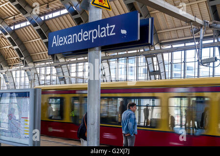 Man waits for an approaching S Bahn train on Alexanderplatz Station station ,Berlin , Germany - Stock Photo