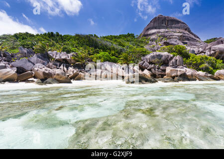 Turquoise water, beach and granite mountains at Anse Source D'Argent in La Digue, Seychelles seen from the water - Stock Photo