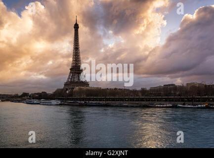 Luminous clouds the Eiffel Tower and the Seine River at sunrise. Port de Suffren, Paris, France - Stock Photo