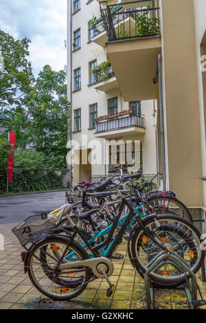 A collection of bicycles parked on a cobbled street - Stock Photo