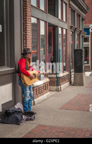 Country music street performer playing guitar and singing on Lower Broadway in The District of downtown Nashville, - Stock Photo