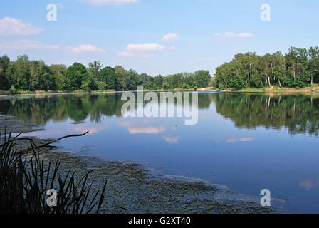 Male Kalisovo jezero water reservoir near Bohumin city and Odra river with trees around and blue sky with clouds - Stock Photo