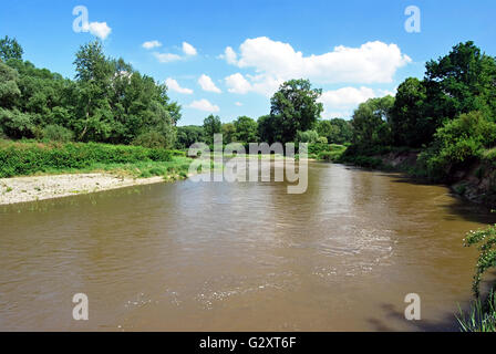 Odra river with trees around and blue sky with clouds on czech-polish boundaries near Bohumin and Chalupki cities - Stock Photo