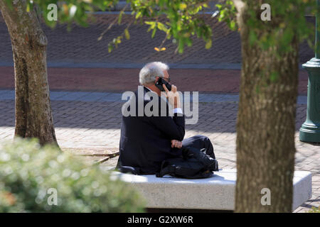 Businessman in a suit with white hair talks on a mobile phone - Stock Photo