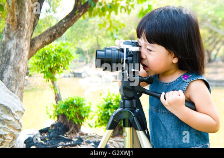 Two years old little girl taking photograph using single lens reflex camera on tripod outdoor in a park. Kid have - Stock Photo