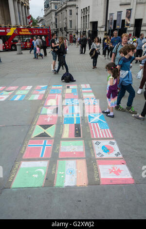 Pavement art in Trafalgar Square, London, UK - colourful chalk drawings of national flags - Stock Photo