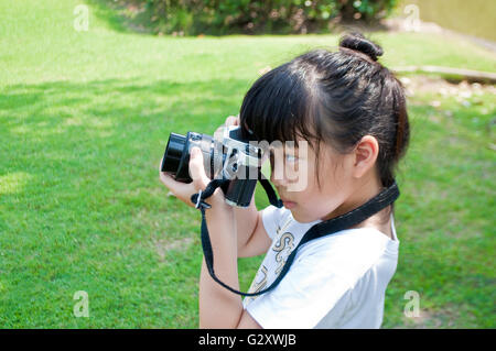 Seven years old girl taking photograph using single lens reflex camera outdoor in a park. Kid have fun practicing - Stock Photo
