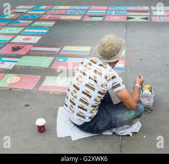 Pavement artist in Trafalgar Square, London, UK - colourful chalk drawings of national flags - Stock Photo