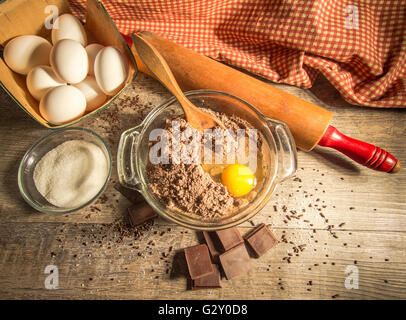 Baking A Chocolate Cake. Preparing chocolate cake batter surrounded by fresh ingredients, wooden spoon and chocolate. - Stock Photo