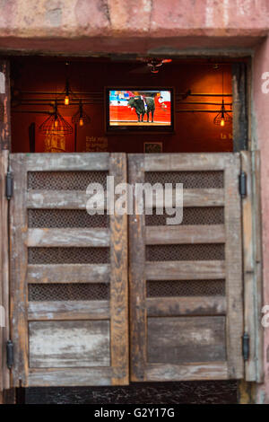 A bull fight plays on the television past the swinging doors on a traditional cantina in San Miguel de Allende, - Stock Photo