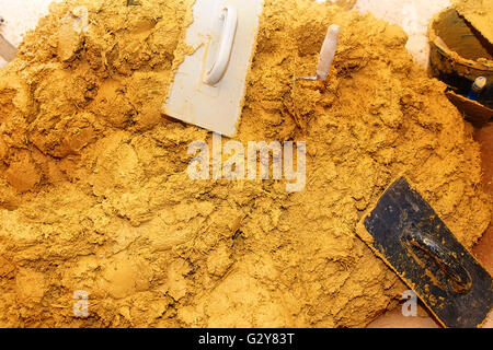 Preparing for the mass natural clay plasters with working tools - Stock Photo