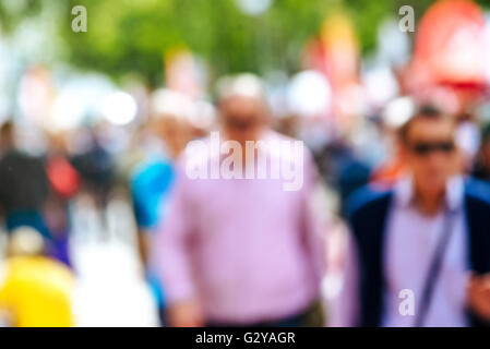 Urban street with pedestrians out of focus, unrecognizable everyday people in urban environment - Stock Photo
