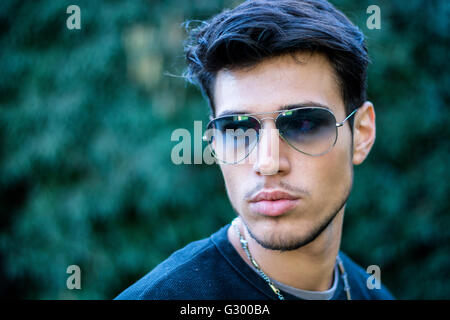 Headshot of handsome young man in city street, looking to a side, wearing sunglasses - Stock Photo
