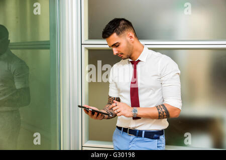 Handsome young businessman in his office working and using tablet PC, looking down, serious - Stock Photo