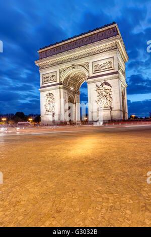 The Arc de Triomphe in Paris at night - Stock Photo