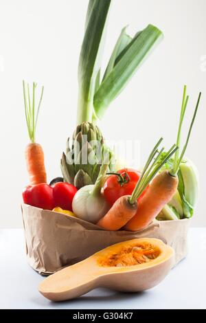 Selection of fresh vegetables in brown paper bag. - Stock Photo