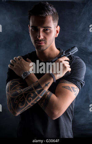 Young handsome man holding a hand gun, wearing black t-shirt, arms crossed on chest, on dark background in studio - Stock Photo
