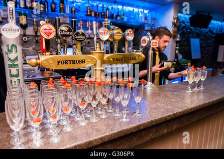 A barman pours champagne into glasses with strawberries at the Portrush Yacht Club, Northern Ireland - Stock Photo