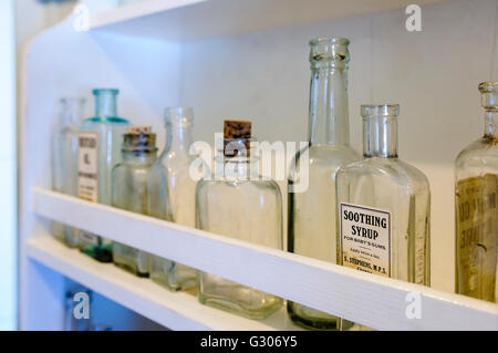 Bottles on shelves within a doctor's surgery from WW1. - Stock Photo