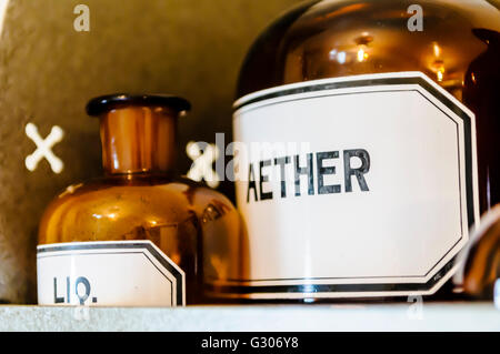 Bottles, including aether (ether) anaesthetic on shelves within a doctor's surgery from WW1. - Stock Photo