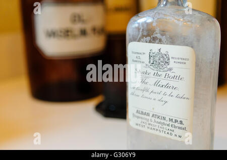 Bottles on shelves within a doctor's surgery from WW1 including one from Alban Atkin, West Hampstead, England - Stock Photo