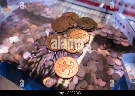 Two-pence coins lie on the glass on top of a 2p nudger machine in a seaside amusement arcade. - Stock Photo