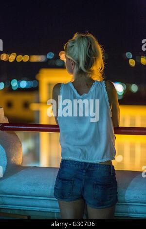 Blonde european traveler looks out over Santiago de Cuba, Cuba - Stock Photo