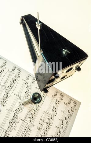 Metronome and mouthpiece of a trumpet isolated on a blank white background  as copy space - Stock Photo