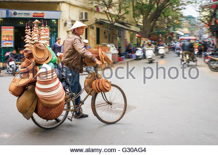 Man on bicycle selling Vietnamese hats in Old Quarter, Hoan Kiem District, Hanoi, Vietnam, Indochina, Southeast - Stock Photo