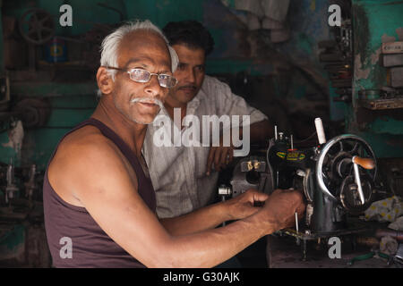 Man repairing an old sewing machine in the city of Jodhpur, Rajasthan, India, Asia - Stock Photo