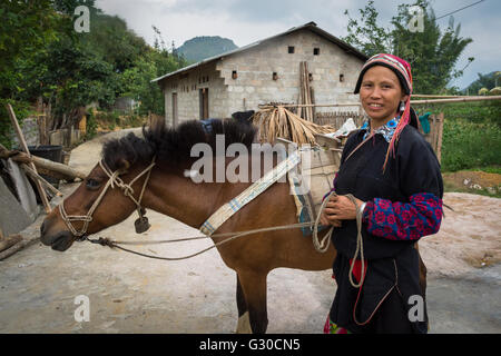 Red Dao woman and her horse on the farm of the Ly Dai Duyen Guest House, Nam Dan, Ha Giang Province, Vietnam. - Stock Photo