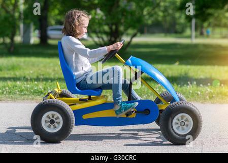 Little girl riding on pedal karting. - Stock Photo