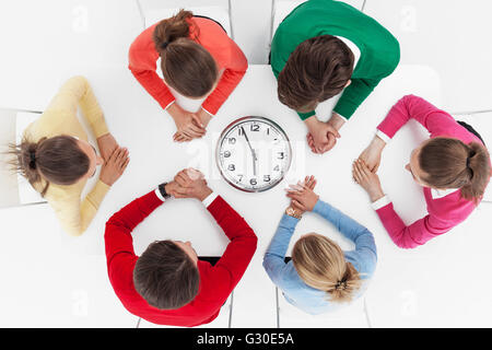 Group of people sitting around wall clock and waiting for time to come - Stock Photo