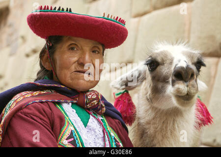 Portrait of old peruvian quechua woman in traditional clothes with llama in Cusco - Stock Photo