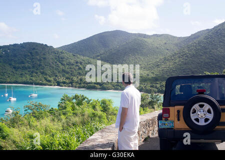 Man taking in the scenery and Maho Bay from an overlook on St. John, US Virgin Islands - Stock Photo